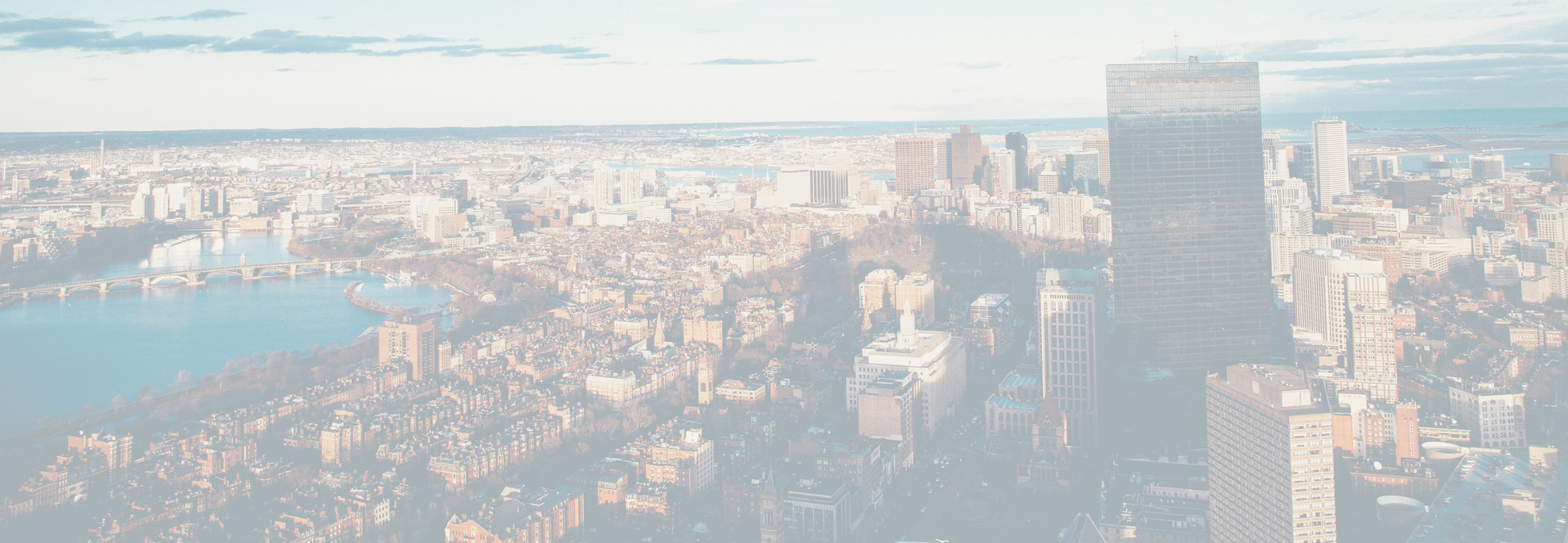 A faded out photo of Boston with sky scrapers in the foreground and water in the background.