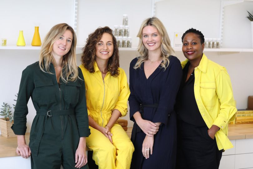 4 women sitting or leaning on a counter, smiling for the camera.