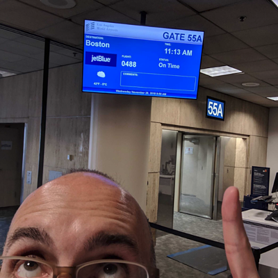 A man in an airport, looking and pointing up to a monitor that shows the gate number, time and location for a flight.