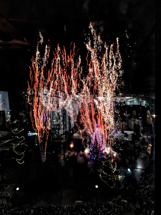An abstract image of sparkling lights and red lines reflected in dark glass.