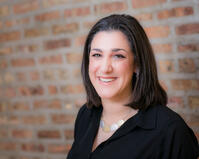 Abby Bangser has dark hair and is wearing a black shirt. She is a senior DevOps practitioner.