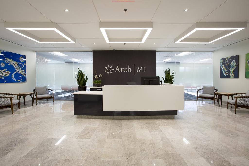 The lobby of the Arch MI office building with a large reception desk in the center, paintings on the wall and a glass wall.