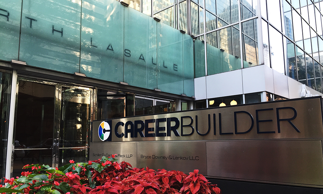 The outside front of a large office building with poinsettias in front of a metal sign that says Career Builder.