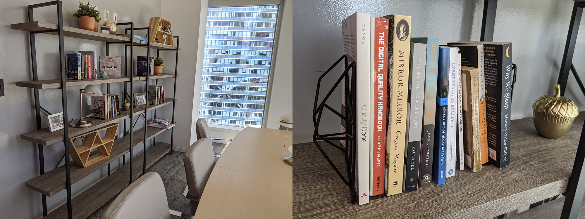 A conference table and a shelf against the wall with books, potted plants and framed pictures.
