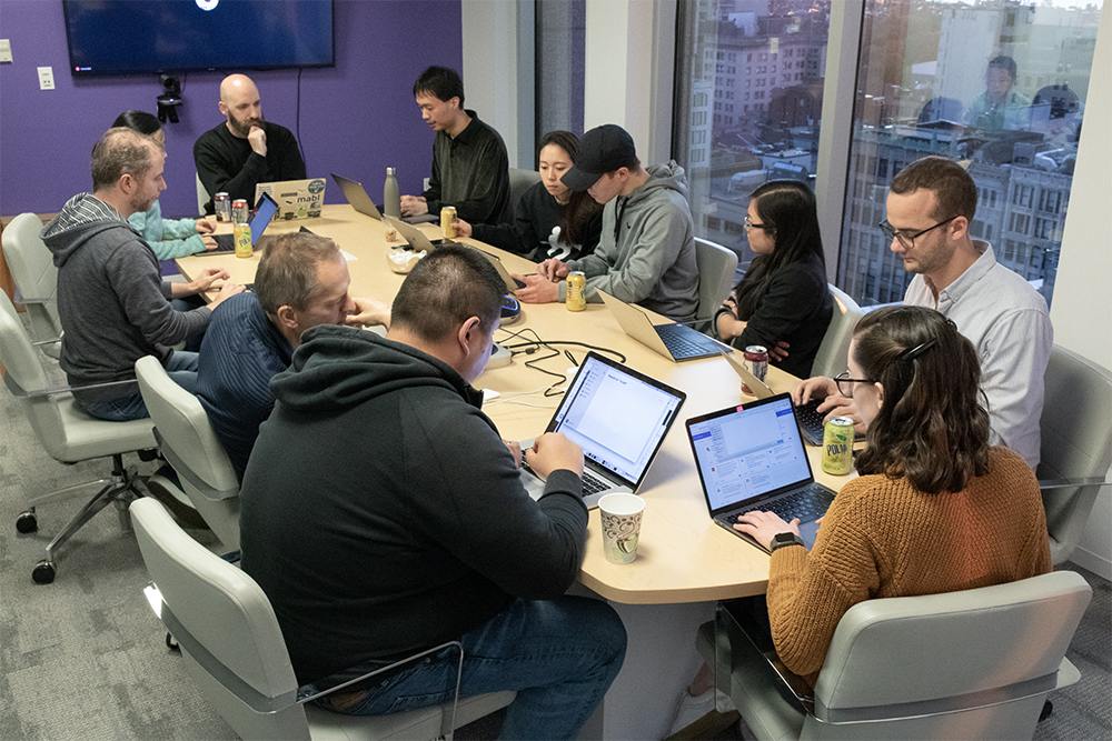 A group of mabl employees working around a conference table.