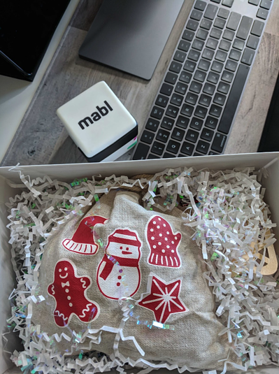 A Christmas present on a desk with a keyboard and a mabl cube.