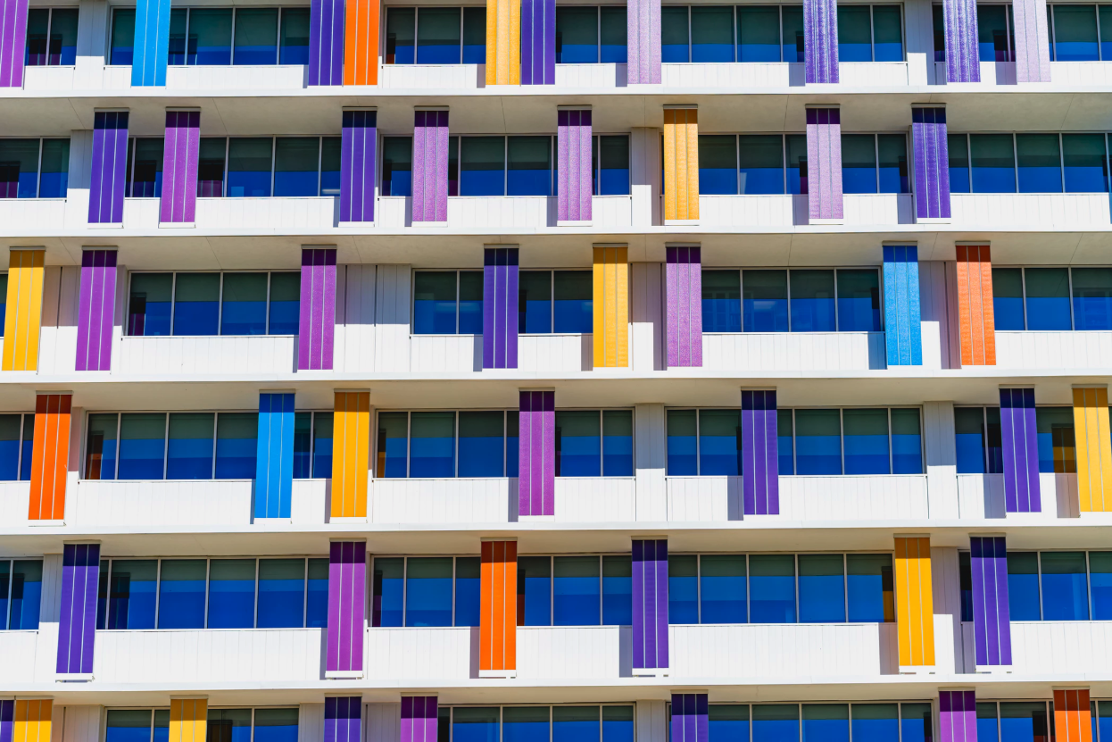 The side of a multistory building with lots of windows and the support pillars are teal, peach, purple, magenta and orange.
